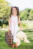 Chica joven que sostiene un oso de la maleta y de peluche imagen de archivo