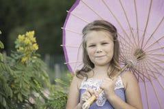 Chica joven que sostiene un paraguas en un jardín Imágenes de archivo libres de regalías