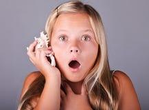 Chica joven que sostiene un seashell Imagen de archivo libre de regalías