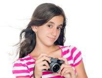 Chica joven que sostiene una cámara compacta con su pelo que flota en th Fotografía de archivo