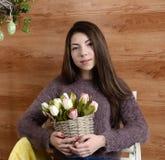 Chica joven que sostiene una cesta de tulipanes Foto de archivo