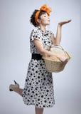 Chica joven que sostiene una cesta y que envía un beso del aire Imagen de archivo libre de regalías