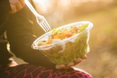 Chica joven que sostiene una ensalada en puesta del sol Fotos de archivo
