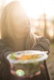 Chica joven que sostiene una ensalada en puesta del sol Foto de archivo libre de regalías
