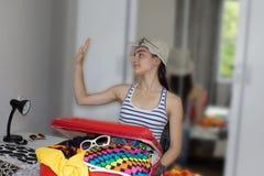 Chica joven que sueña con un viaje del mundo Maletas del embalaje de la chica joven en piso en casa Fotografía de archivo