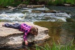 Chica joven que sumerge su mano en el agua Foto de archivo