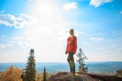 Chica joven que tiene un resto en la cima de la montaña Concepto tranquilo meditación Amor de la naturaleza Foto de archivo