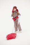 Chica joven que tira del trineo el día de fiesta del esquí Foto de archivo