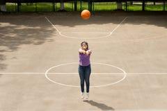 Chica joven que tira un baloncesto Foto de archivo libre de regalías