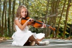 Chica joven que toca el violín en las maderas. Foto de archivo