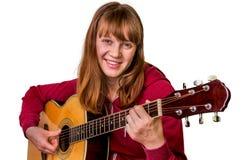 Chica joven que toca la guitarra acústica - aislada en blanco Imagenes de archivo