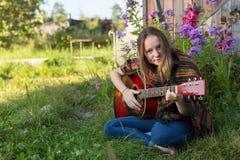 Chica joven que toca la guitarra acústica que se sienta al aire libre hippie Imagenes de archivo