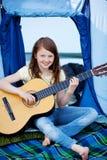 Chica joven que toca la guitarra contra la tienda Imagen de archivo libre de regalías