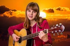 Chica joven que toca la guitarra en la puesta del sol Foto de archivo libre de regalías