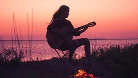 Chica joven que toca la guitarra en la playa con la hoguera en la puesta del sol almacen de metraje de vídeo