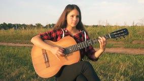 Chica joven que toca la guitarra en prado en la puesta del sol almacen de metraje de vídeo