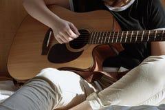 Chica joven que toca la guitarra y que se sienta en la cama Foto de archivo