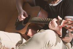 Chica joven que toca la guitarra y que se sienta en la cama Fotografía de archivo