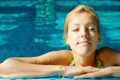 Chica joven que toma el sol en la piscina Imágenes de archivo libres de regalías
