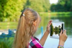 Chica joven que toma la foto del lago por la PC de la tableta Fotografía de archivo libre de regalías