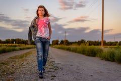 Chica joven que toma un paseo de la tarde en el país Fotos de archivo libres de regalías