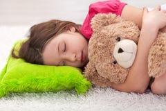 Chica joven que toma una siesta con su oso de peluche Fotografía de archivo