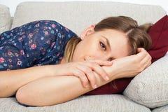 Chica joven que toma una siesta en casa Foto de archivo libre de regalías
