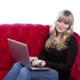 Chica joven que trabaja con la computadora portátil Imagen de archivo