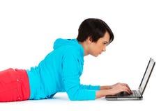 Chica joven que trabaja en la computadora portátil aislada Imagenes de archivo