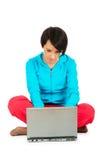 Chica joven que trabaja en la computadora portátil aislada Imagen de archivo libre de regalías