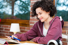 Chica joven que trabaja en la tableta. Imagen de archivo