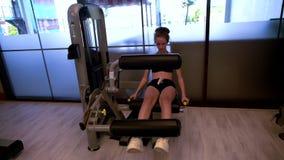 Chica joven que usa el ab y la máquina trasera en gimnasio almacen de metraje de vídeo