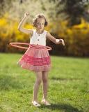 Chica joven que usa el aro del hula en un parque Foto de archivo libre de regalías