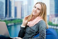 Chica joven que usa el ordenador portátil en butaca cómoda con la ciudad grande en el b Foto de archivo