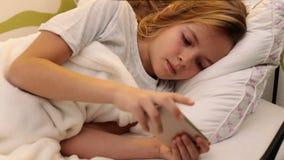 Chica joven que usa el smartphone que manda un SMS en cama almacen de metraje de vídeo