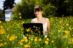 Chica joven que usa la computadora portátil Imagenes de archivo
