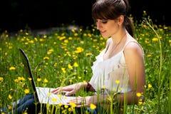 Chica joven que usa la computadora portátil Imagen de archivo libre de regalías