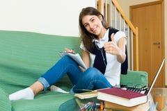 Chica joven que usa la computadora portátil en el país Foto de archivo