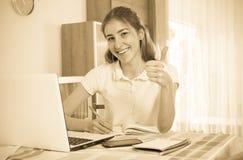 Chica joven que usa la computadora portátil en el país Foto de archivo libre de regalías