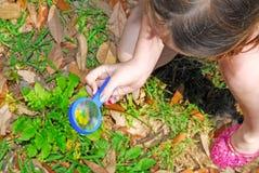 Chica joven que usa la lupa Imagen de archivo libre de regalías