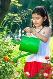 Chica joven que usa la regadera al aire libre Foto de archivo