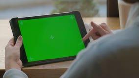 Chica joven que usa la tableta con la pantalla táctil para la navegación por Internet en línea y la lectura del email Dispositivo almacen de video