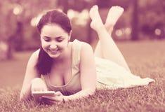 Chica joven que usa la tableta digital mientras que miente en lepisosteus verde de la primavera Imagenes de archivo