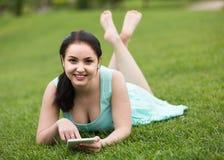 Chica joven que usa la tableta digital mientras que miente en lepisosteus verde de la primavera Imagen de archivo libre de regalías