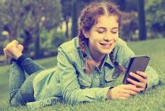 Chica joven que usa la tableta digital mientras que miente en lepisosteus verde de la primavera Fotografía de archivo