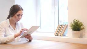 Chica joven que usa la tableta en el trabajo almacen de video