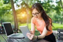 Chica joven que usa la tableta y el ordenador portátil fotografía de archivo