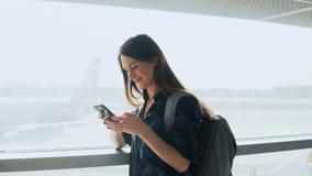 Chica joven que usa smartphone cerca de ventana del aeropuerto La mujer europea feliz con la mochila utiliza el app móvil en term foto de archivo libre de regalías