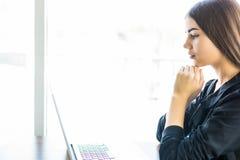 Chica joven que usa su ordenador portátil en cafetería y mirada en la pantalla Imagen de archivo libre de regalías