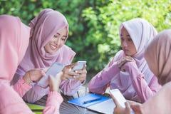 Chica joven que usa su propio smartphone e ignorando a su amigo Imágenes de archivo libres de regalías